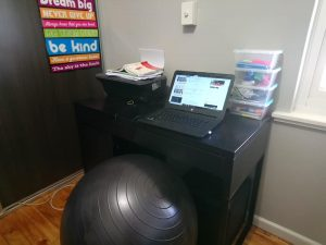 Computer on small desk with gym ball instead of a chair.