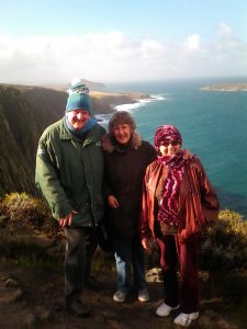 A man and two women on the clifftop with stunning views of water and rock behind