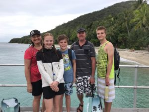 Family photo with background of blue-green waters, sandy beach and lush vegetation on a hill