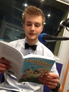 Young man in radio studio reading from 'Three dummies in a dinghy'