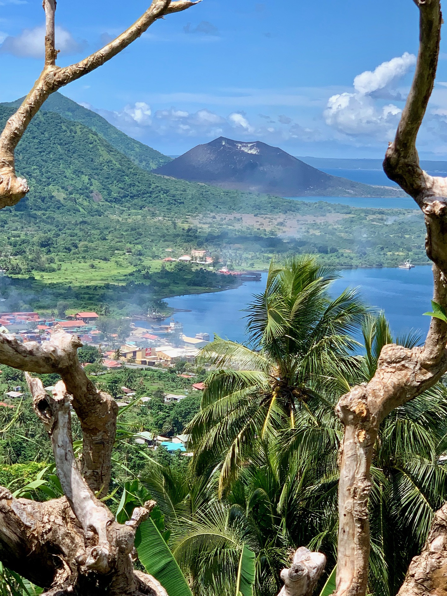 Picture of Rabaul: a blue lake surrounded by hills and palm trees and a village.